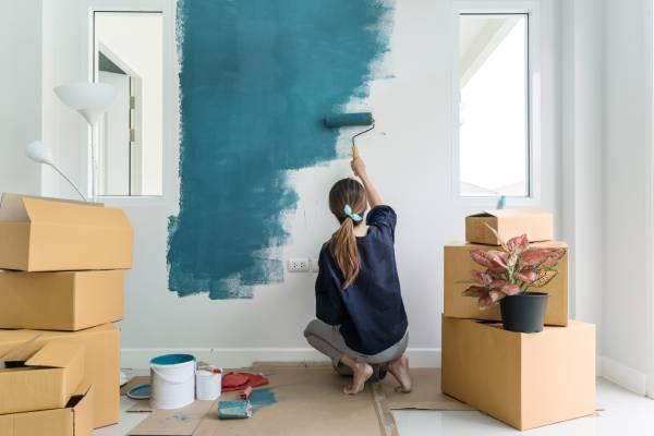 Jeune femme en train de repeindre son mur avec une peinture pour intérieur